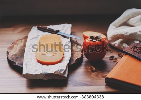 fresh persimmon slices on wooden table with notebook and knitted sweater, cozy lifestyle setting, selective focus - stock photo