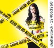 fresh photo of a crime scene with undead female victim still walking while being tied up with yellow tape - stock photo