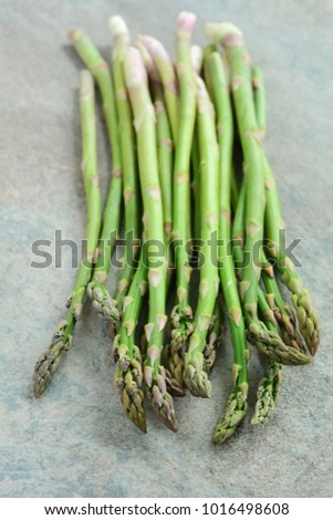 Fresh picked asparagus on textured background in vertical format with selective focus on tips