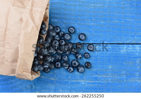 Fresh picked blueberries spilling out of a brown paper bag onto a rustic blue wood table. Horizontal format with copy space shot from a high angle. - stock photo