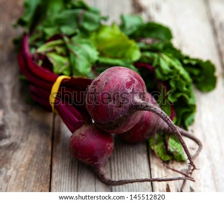 Fresh picked bunch of organic beetroot on wooden table, horizontal - stock photo