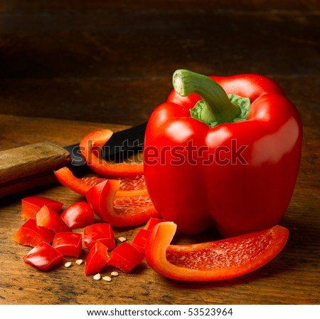 Fresh picked red bell pepper cut into pieces on rustic cutting board. - stock photo