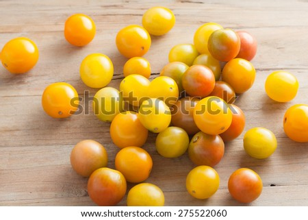 fresh picked ripe organic colorful mini tomatoes on rustic wooden background, top view - stock photo