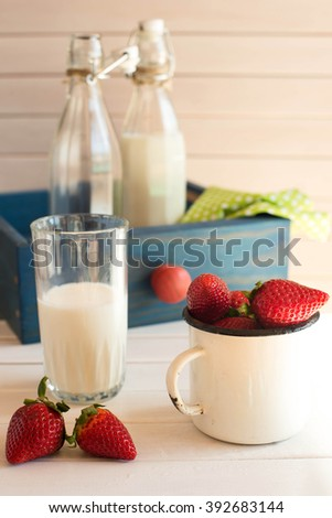 Fresh picked strawberrys with glass of the milk on white wooden background. Rustic style.