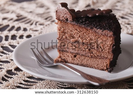 Fresh piece of chocolate cake on a plate on a table close-up. horizontal