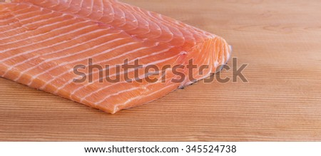 Fresh piece of salmon fillet. Raw fish on wooden cutting board