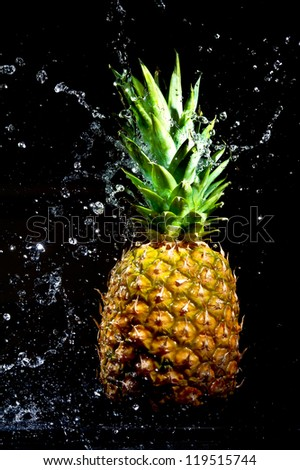 Fresh pineapple in water drops on black background - stock photo