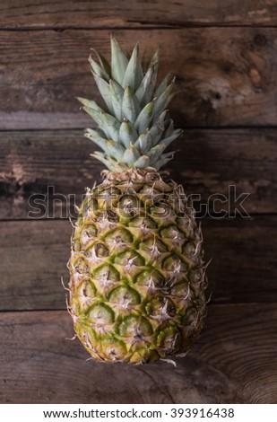 fresh pineapple on wooden background - stock photo