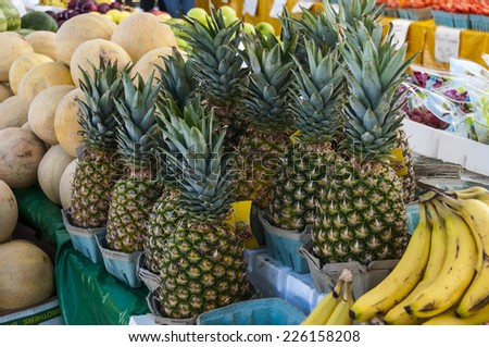 Fresh Pineapples and other fruit at a farmers market ready to sell - stock photo