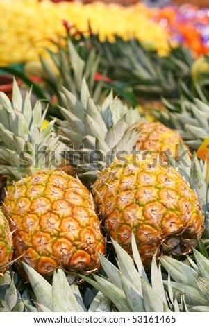 Fresh pineapples in a marketplace - stock photo