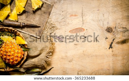 Fresh pineapples, whole and sliced in a basket on old fabric. On a wooden table. Free space for text . Top view - stock photo