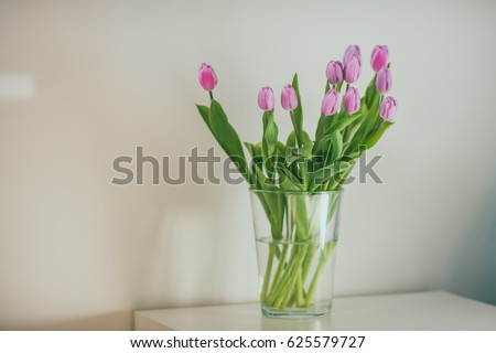 Fresh pink tulip flowers bouquet in a glass jar on white table