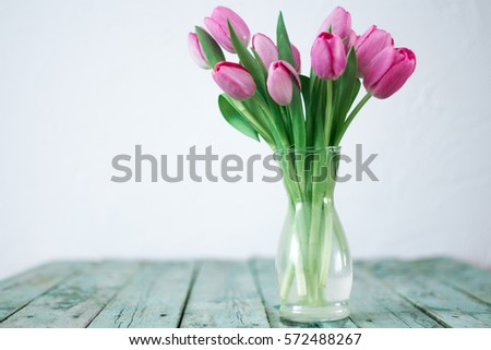 Fresh pink tulip flowers bouquet on shelf in front of wall. View with copy space,Spring holiday concept