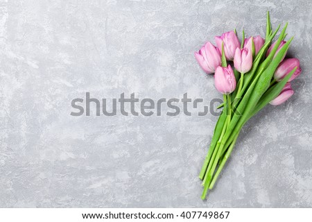 Fresh pink tulip flowers on stone table. Top view with copy space