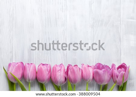 Fresh pink tulip flowers on wooden table. Top view with copy space - stock photo