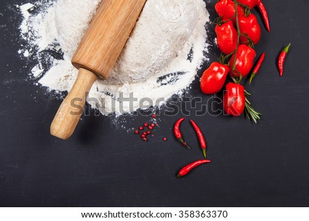 Fresh pizza dough with natural ingredients for cooking on black table - stock photo