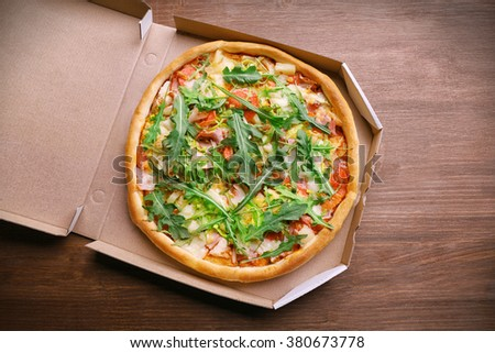 Fresh pizza in carton box on wooden table, top view - stock photo