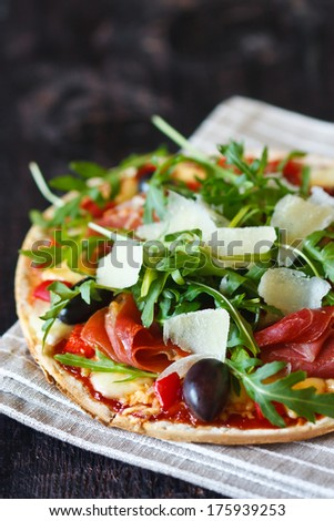 Fresh pizza with ham,olives, arugula and parmesan cheese flakes on a linen napkin.
