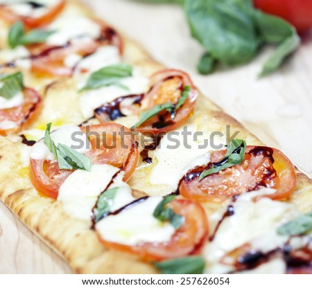 Fresh pizza with tomato, mozzarella and basil on wooden board - stock photo