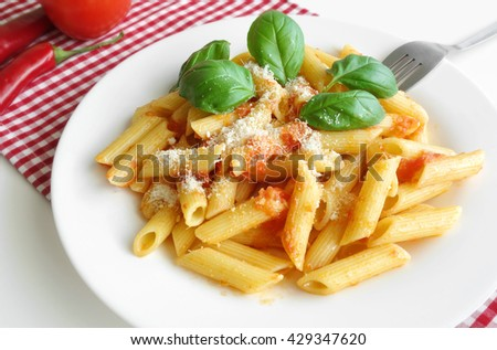Fresh plate of pasta penne with tomato sauce, parmesan and basil mediterranean food background.