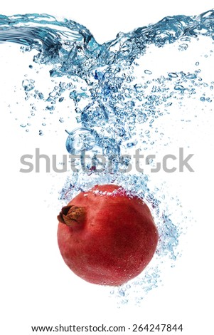 Fresh Pomegranate dropped into water with splash isolated on white - stock photo