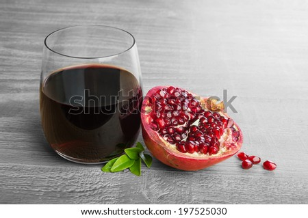 Fresh pomegranate fruit and pomegranate juice over wooden vintage table - stock photo