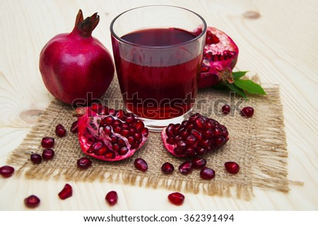 Fresh pomegranate juice in a glass with fruit pomegranates on a wooden background - stock photo