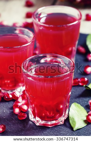 Fresh pomegranate juice on a black background, selective focus