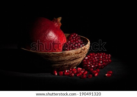 Fresh pomegranate with grains on black background.