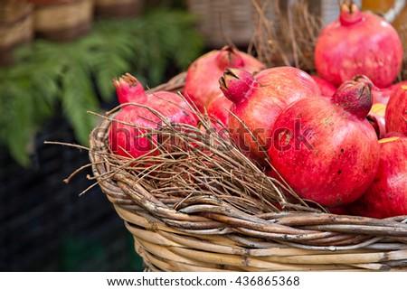 Fresh pomegranates are at the basket - stock photo