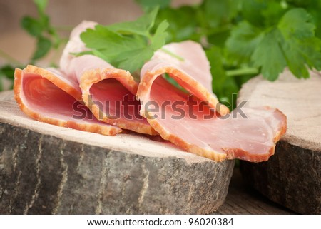 Fresh pork ham with garnish on wooden background - stock photo