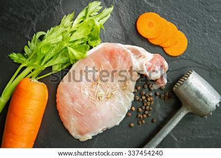 Fresh pork meat with pepper, rosemary, carrot, celery  and meat hammer on black stone. - stock photo