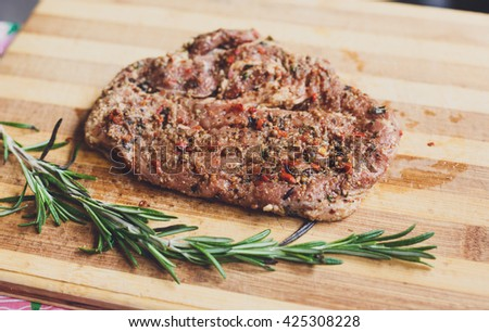 Fresh pork steak ready for BBQ cooking. Raw meat on a cutting board with rosemary leaf. Raw pork meat on wood, closeup. Marinated in spices raw steak for barbecue. - stock photo