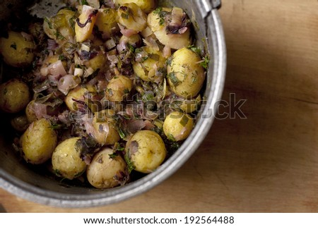 Fresh potato with vegetables in traditional cast-iron kettle on wood table - stock photo
