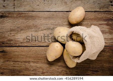 Fresh potatoes in hemp sack bags on rustic wooden background. Raw organic potatoes on old wooden background. - stock photo