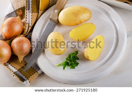 Fresh potatoes on a white cutting board. - stock photo