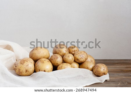 Fresh potatoes on the old wooden table