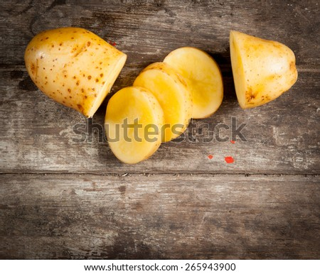 Fresh potatoes on the wood background - stock photo