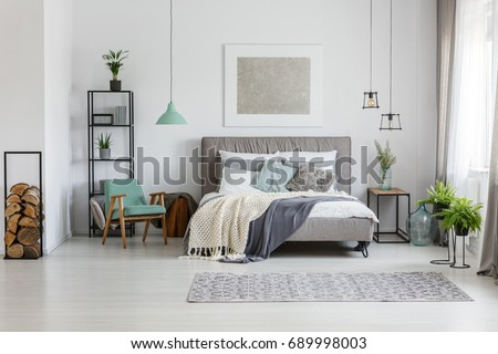 Fresh potted plants in bright room with poster above the bed