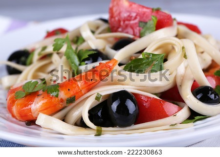 Fresh prawns with spaghetti, olives, tomatoes and parsley in big round plate closeup