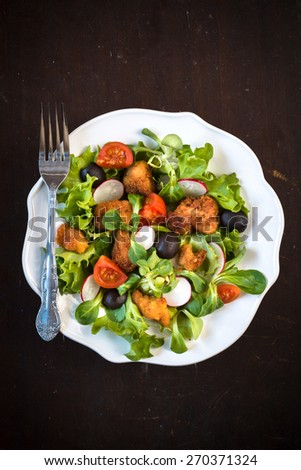 Fresh prepared chicken salad with vegetables in the plate on wooden background,selective focus and blank space - stock photo