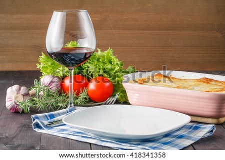 Fresh prepared lasagna with ingredients on table - stock photo