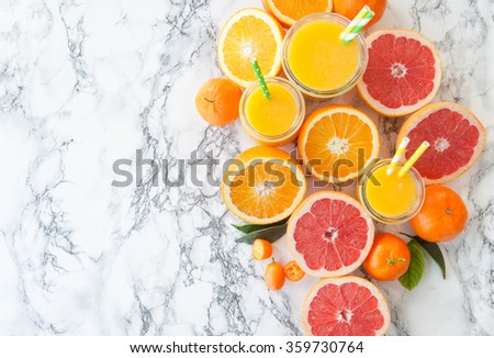 Fresh pressed juice from colorful citrus fruits - stock photo