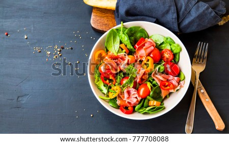 Fresh prosciutto ham and vegetables salad with spinach , tomatoes , peppers and ham seasoned with herbs, top view, healthy spring salad