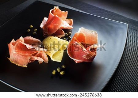 Fresh prosciutto with cheese and capers close up
