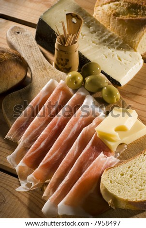 fresh prosciutto with cheese olives and bread close up shoot - stock photo