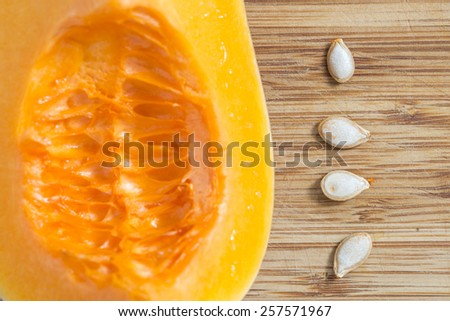 Fresh pumpkin cutting in quarter and four seeds on a bamboo board. on a bamboo board.