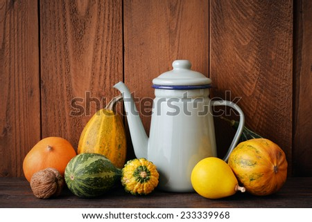 Fresh pumpkins with vintage kettle on wooden background