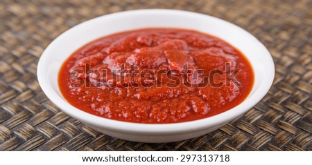 Fresh pureed tomato in white bowl over wicker background - stock photo