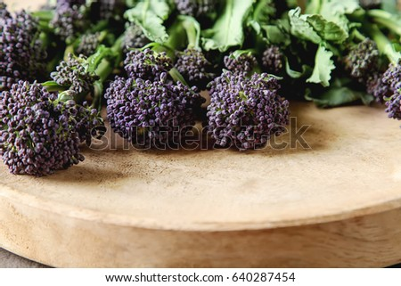 Fresh purple broccoli on a wooden plate. Vegan food. Dark background